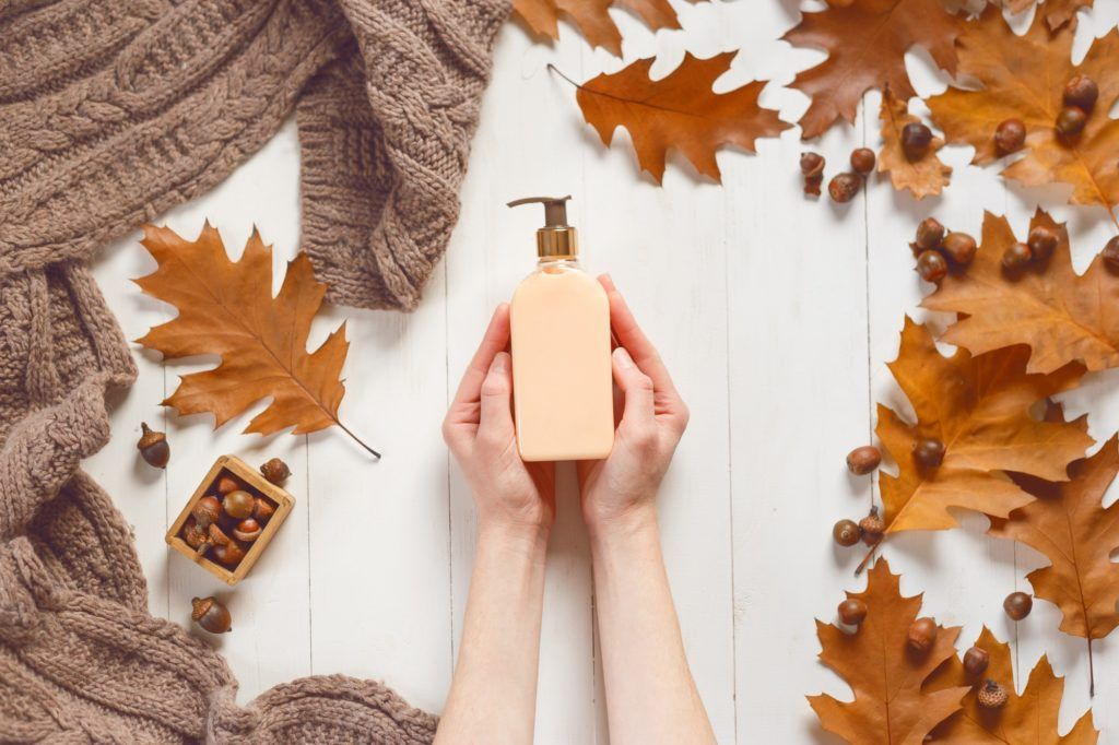 Bottle with liquid soap in female hands on white wooden background with a soft scarf and oak leaves